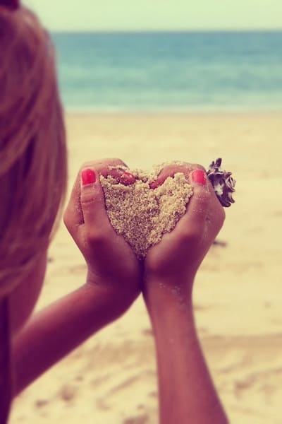 hands holding sand in a heart shape
